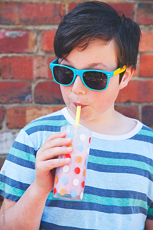 A young boy drinks a strawberry smoothie / milkshake by Natalie JEFFCOTT for Stocksy United
