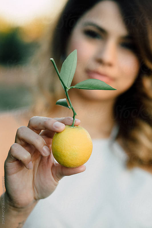 Woman holding freshly picked orange by ZOA PHOTO for Stocksy United