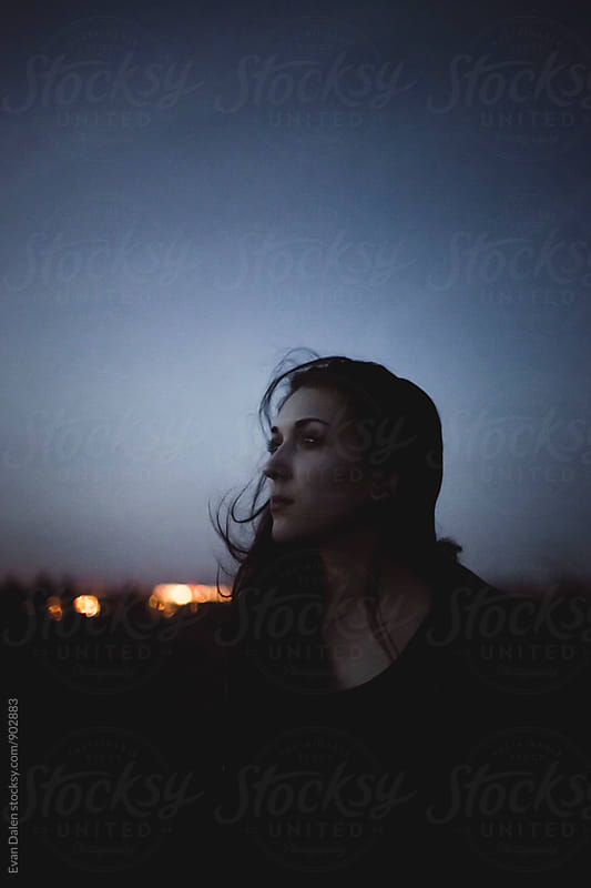 Young Woman Looking at Sky at Dusk by Evan Dalen for Stocksy United