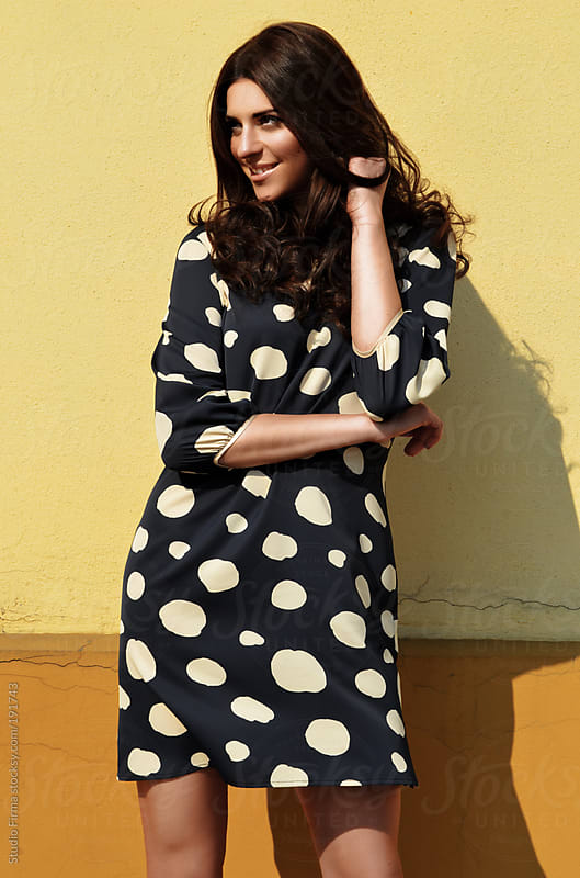 Smiling young woman in polka dot dress by Studio Firma for Stocksy United