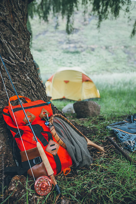 flyfishing gear, backpack, rod and net leaning against a tree in camp by Micky Wiswedel for Stocksy United