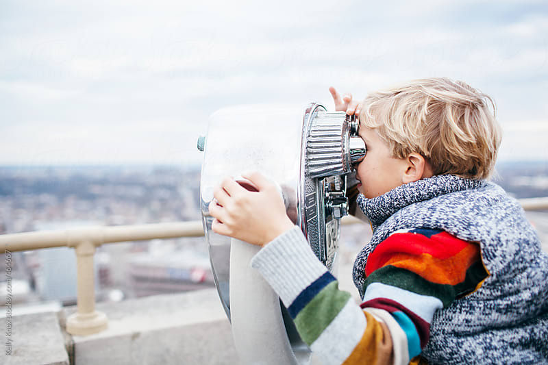 boy looking through coin operated binoculars  by Kelly Knox for Stocksy United