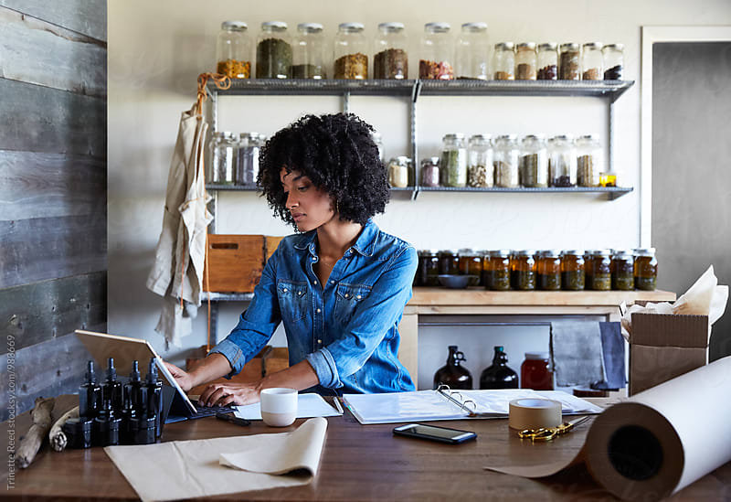 Millennial African American Woman businesswoman working on computer in her skincare studio by Trinette Reed for Stocksy United