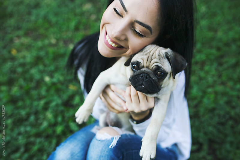 Young woman and a pug dog in nature by Jovana Rikalo for Stocksy United