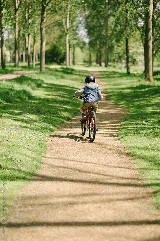 Youth rides his bike along a tree lined path by Rebecca Spencer for Stocksy United