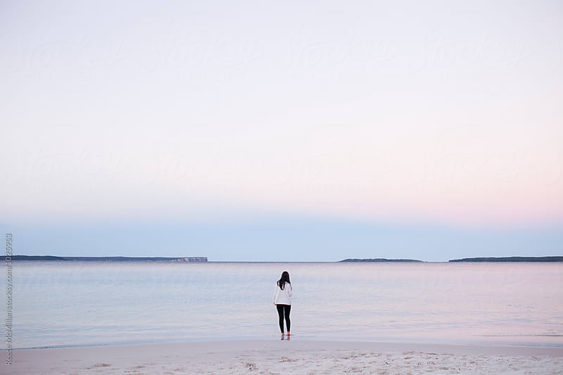 A woman stands at the water's edge of Hyam's Beach, Jervis Bay by Reece McMillan for Stocksy United