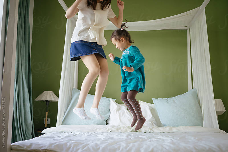 Cute toddler girl playing with her young mother on bed by Maa Hoo for Stocksy United