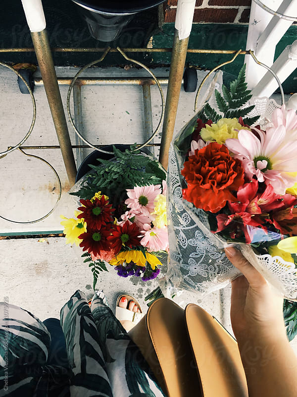 A woman holding flowers at a market by Chelsea Victoria for Stocksy United