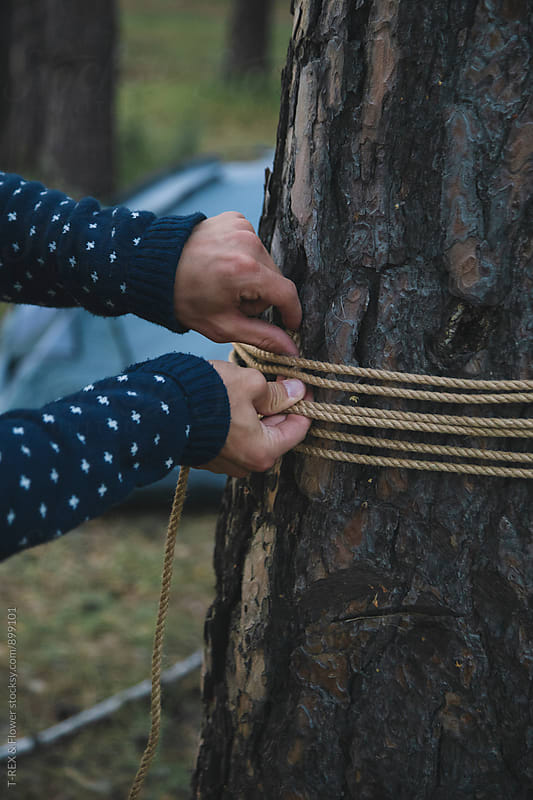 Man tying hammock to tree by Danil Nevsky for Stocksy United