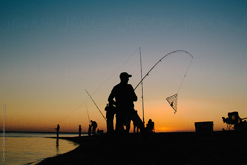 people crabbing at sunset by Cameron Zegers for Stocksy United