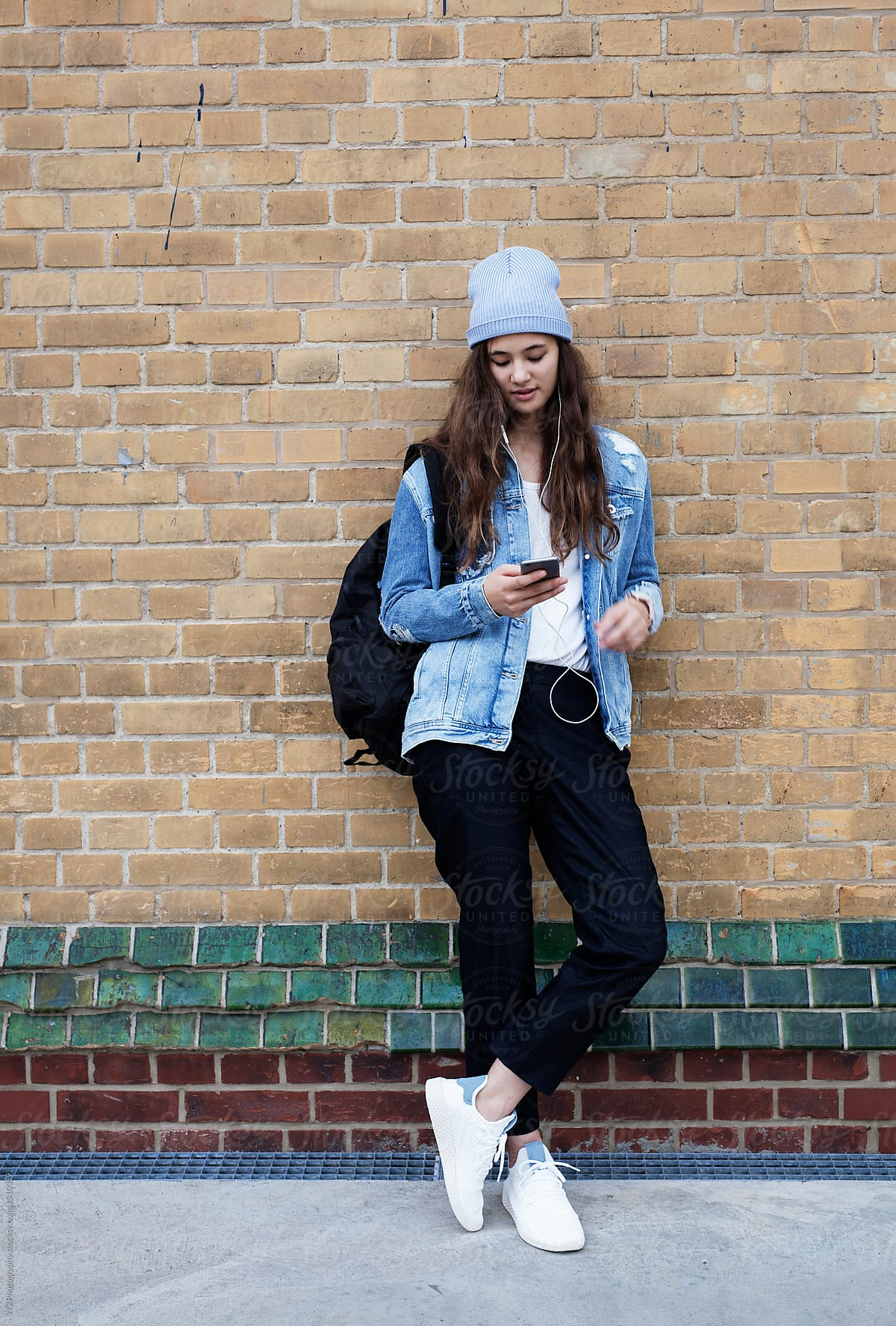 Stock Photo A Young Woman Listening To Music And Leaning On A Brick Wall