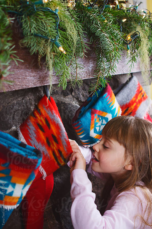 A child peeks into a Christmas stocking hanging from the fireplace mantle by Tana Teel for Stocksy United
