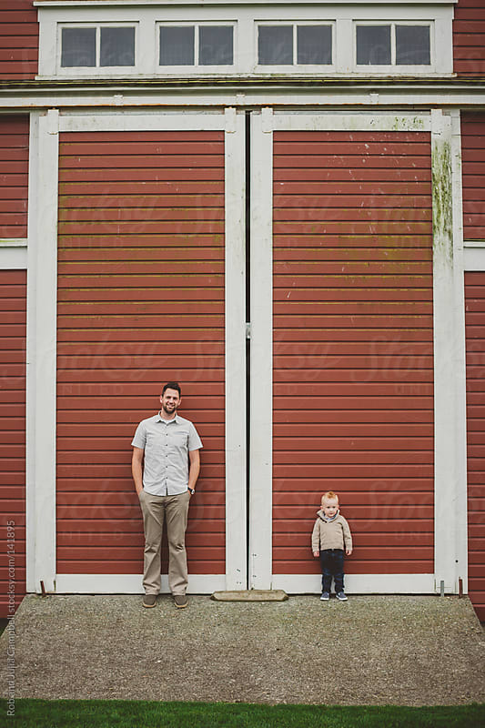 Dad and young son standing in front of red barn door by Rob and Julia Campbell for Stocksy United
