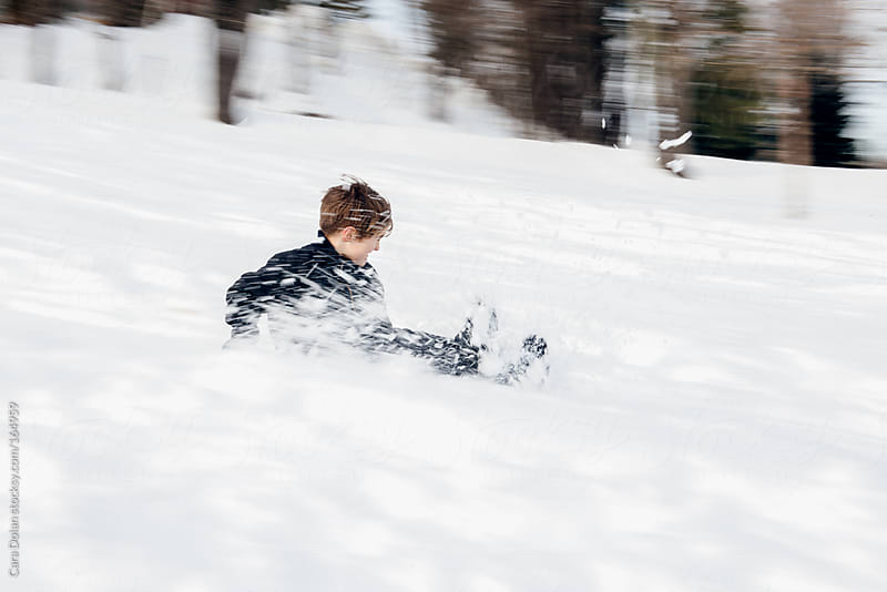 Child in motion sledding down a snowy hill by Cara Dolan for Stocksy United