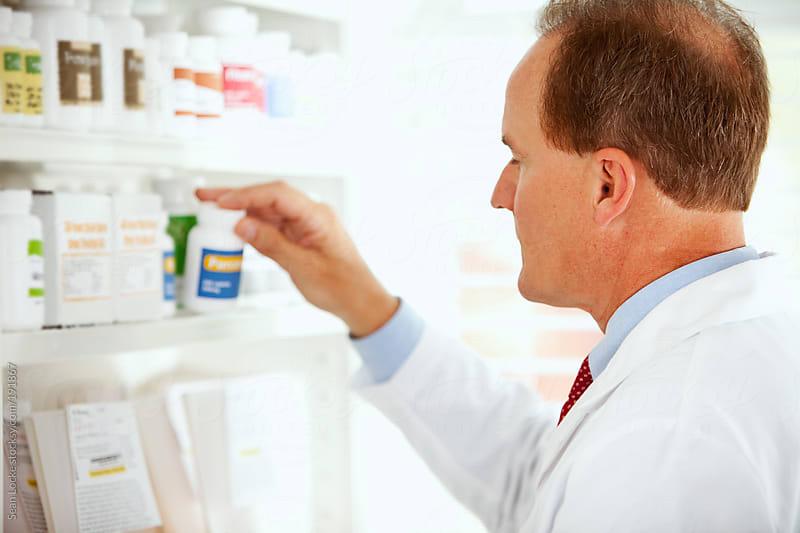 Pharmacy: Male Pharmacist Examines Pill Bottle by Sean Locke for Stocksy United