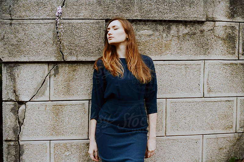 Young woman against old stone wall by Lyuba Burakova for Stocksy United