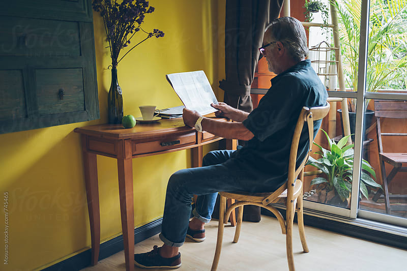 Older Man Reading Newspaper at Home by Mosuno for Stocksy United