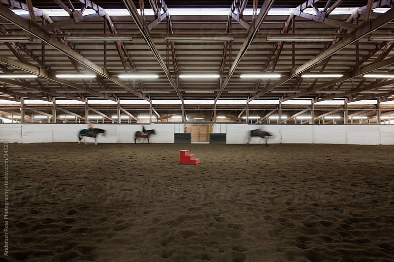 People riding horse in training stable by Andersen Ross Photography for Stocksy United
