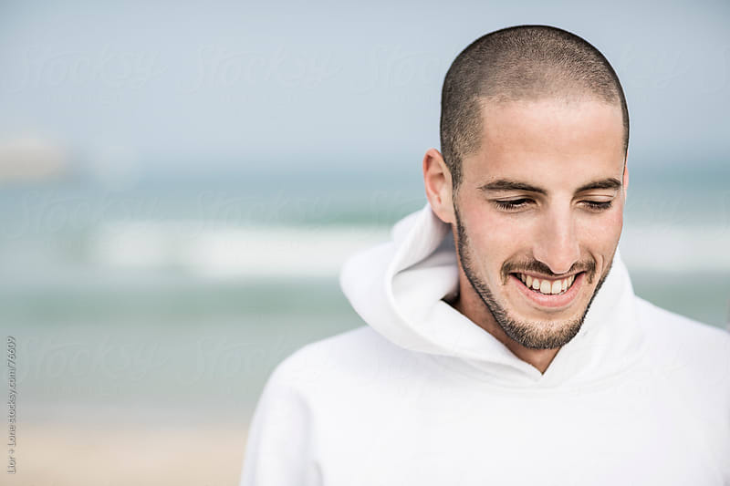 Young man smiling by the sea by Lior + Lone for Stocksy United