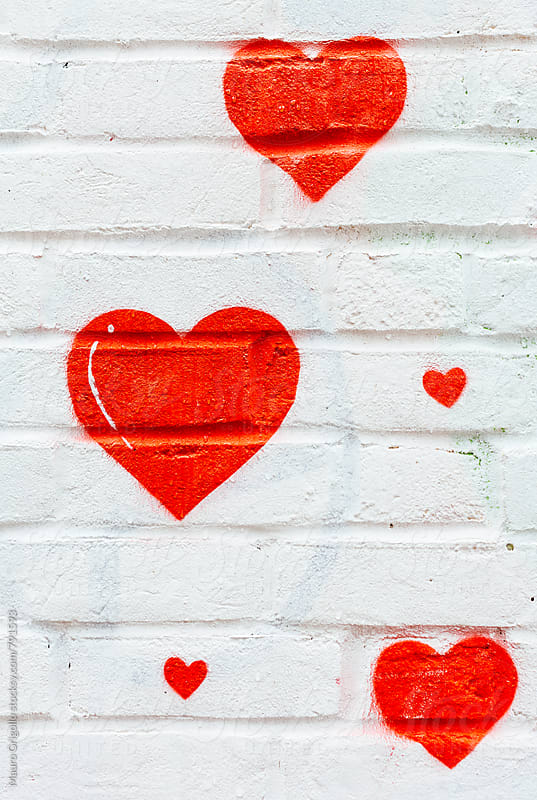 Small red hearts shape  painted on white wall by Mauro Grigollo for Stocksy United