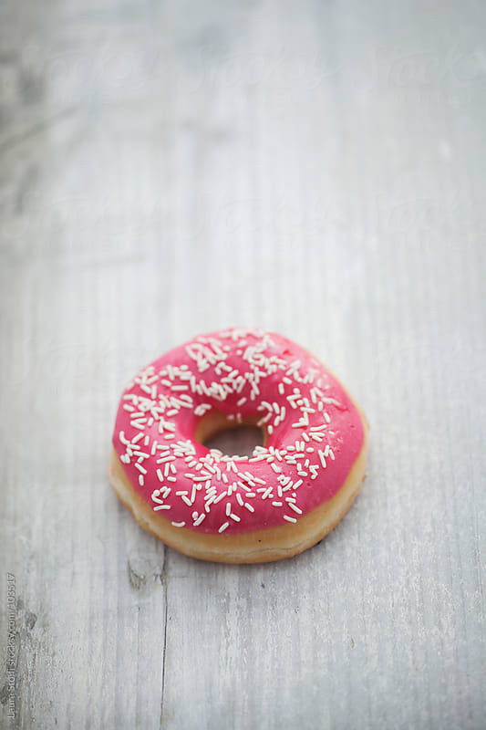 Pink doughnut with white sugary on it on wooden table by Laura Stolfi for Stocksy United