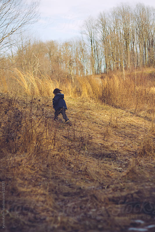 Young Boy Walking Up a Hill by Kevin Keller for Stocksy United