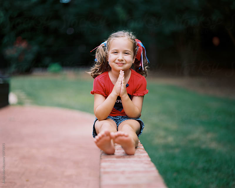 Cute young girl with pigtails sitting on a brick wall by Jakob for Stocksy United