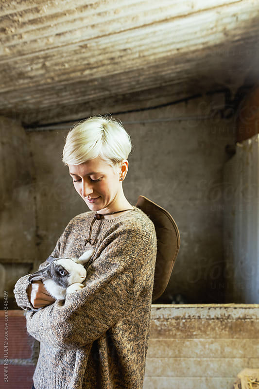 Woman embracing a cute bunny on a farm.  by BONNINSTUDIO for Stocksy United