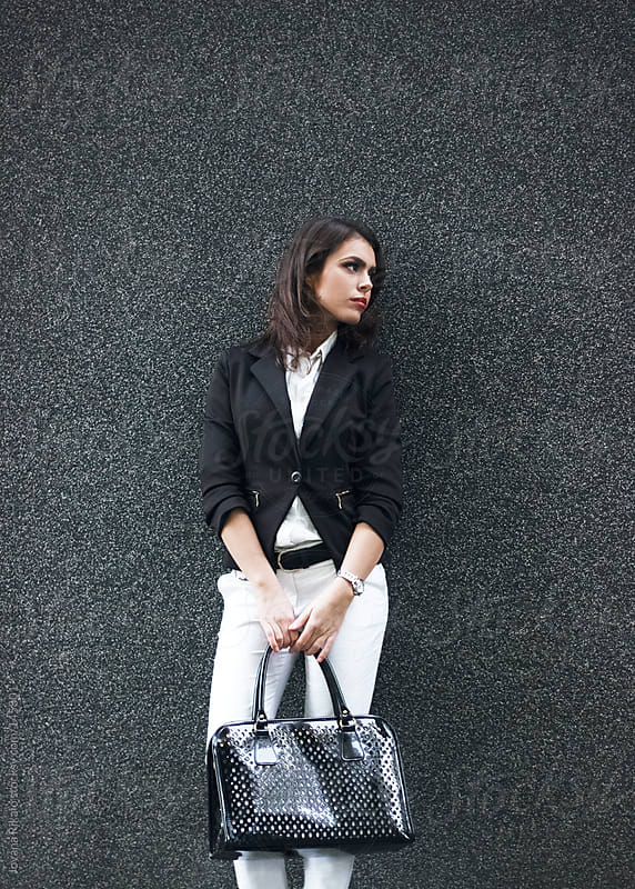 Young businesswoman holding her bag by Jovana Rikalo for Stocksy United