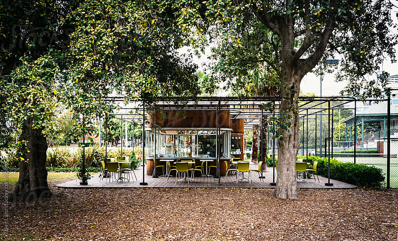 Modern cafe outdoors under trees by Trent Lanz for Stocksy United