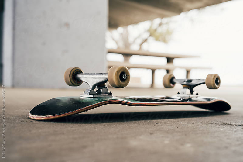 Skateboard on sidewalk by Isaiah & Taylor Photography for Stocksy United