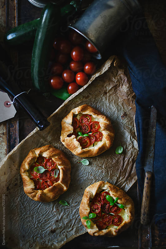 Three homemade vegetarian pastries in a rustic table setting. by Darren Muir for Stocksy United