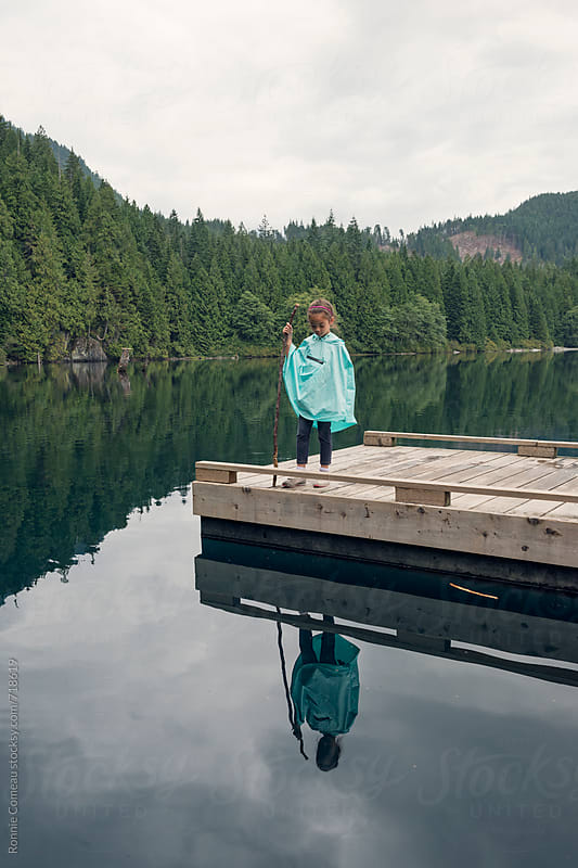 Small Girl With Pancho Standing On Dock by Ronnie Comeau for Stocksy United