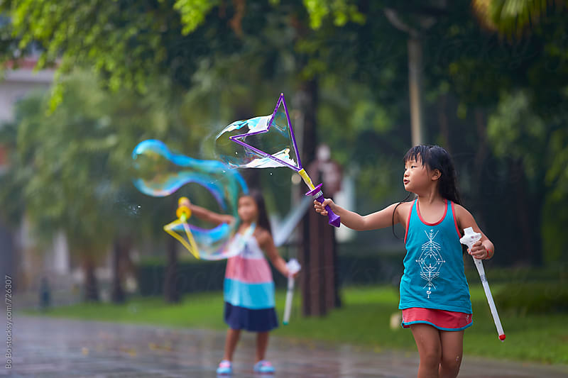 two happy little asian girl playing bubble in the park by Bo Bo for Stocksy United