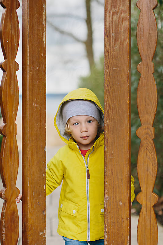 Adorable kid looking through the whole in fence by Amir Kaljikovic for Stocksy United
