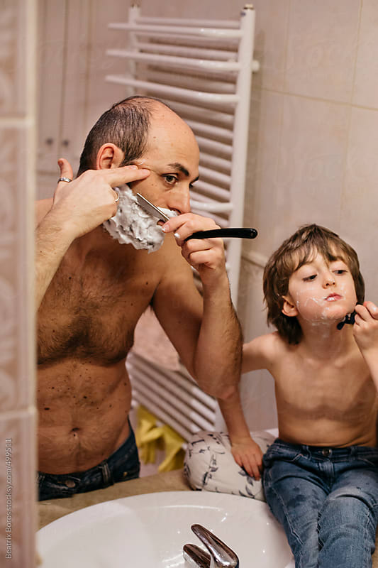 Father and 6 years old son carefully shaving their faces by Beatrix Boros for Stocksy United
