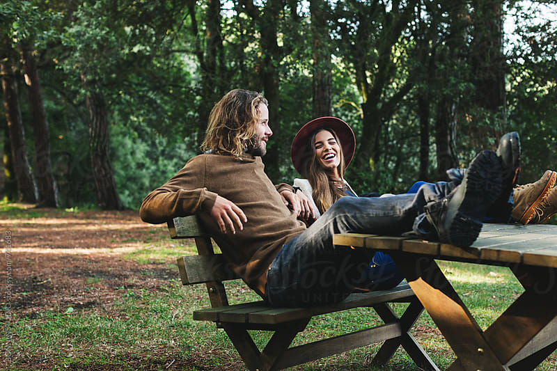 Couple having fun sitting on a bench in the forest. by BONNINSTUDIO for Stocksy United