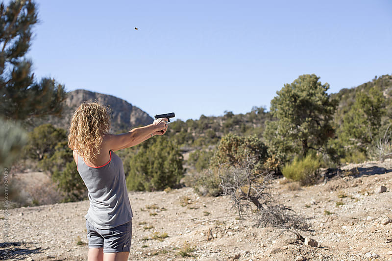 Woman shooting a handgun in the desert by Amy Covington for Stocksy United