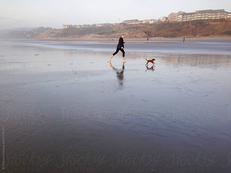 Man Running on Beach with Dog by B. Harvey for Stocksy United