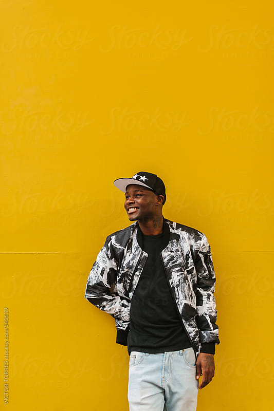 Young Black Man Against a Yellow Wall by VICTOR TORRES for Stocksy United