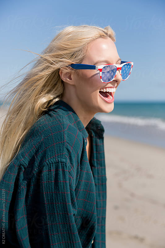 Young blonde woman in sunglasses enjoying the beach. by Robert Zaleski for Stocksy United