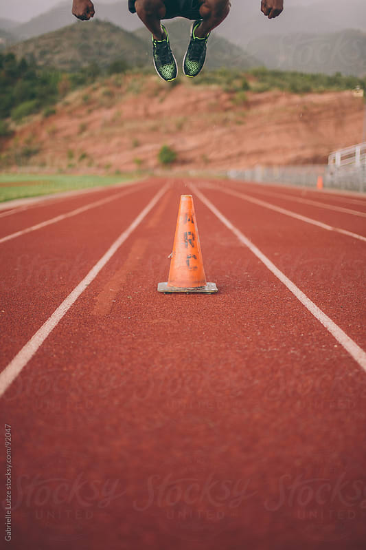 Black guy jumping over an orange cone on a track by Gabrielle Lutze for Stocksy United