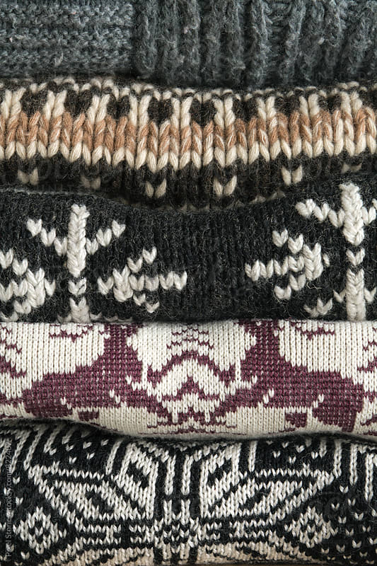 Winter-themed sweaters stacked on a shelf by Pixel Stories for Stocksy United