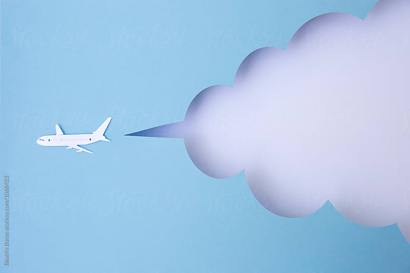 Travel concept: cardboard airplane flying  in front of a cloud mock-up by Beatrix Boros for Stocksy United