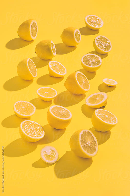 Yellow lemons on a yellow background by Juri Pozzi for Stocksy United