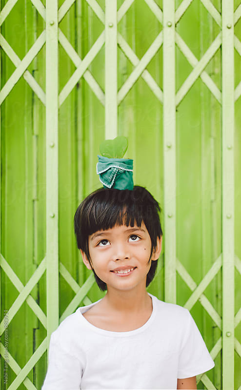 Cute little asian boy with a hoya plant pot on his head by Nabi Tang for Stocksy United