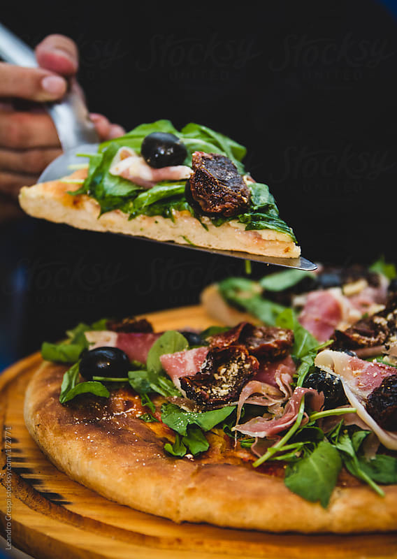 smoked ham pizza with green leaves and dry tomatoes by Leandro Crespi for Stocksy United