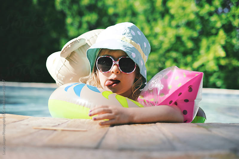 Little girl relaxes in a pool with floaties and sun protection. by Lucas Saugen for Stocksy United