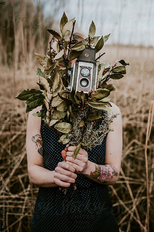 a girl holding a bouquet of dried leaves and an old camera in his hands by Thais Ramos Varela for Stocksy United