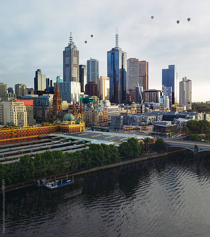 Melbourne city skyline as five hot air balloons quietly explore the city in the early morning light by Angela Lumsden for Stocksy United